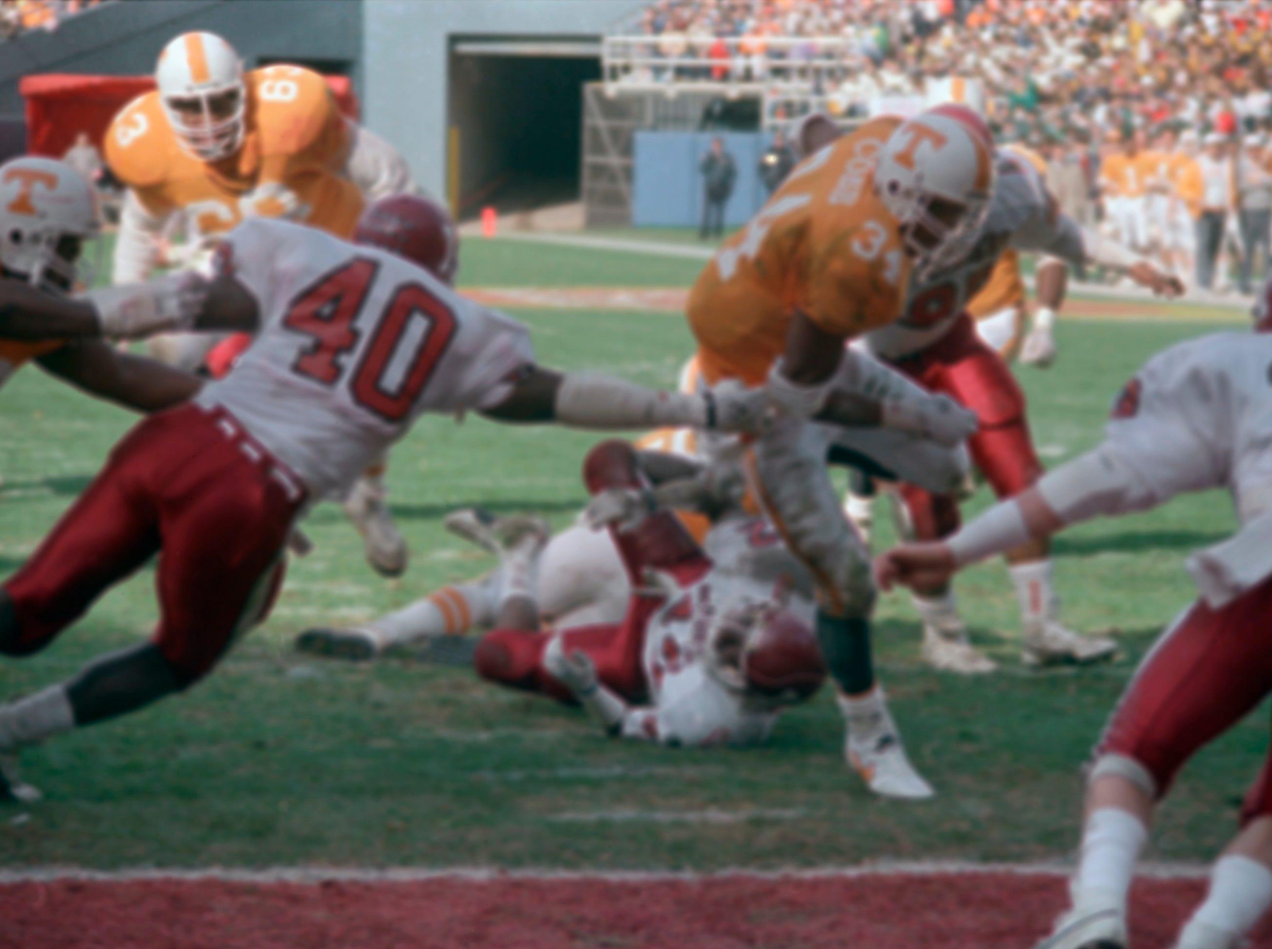 Tennessee running back Reggie Cobb, 34, pulls away from Indiana linebacker Darren Bush, 40, to score in first quarter of their Peach Bowl game at Atlanta Fulton County Stadium in Atlanta, on Jan. 2, 1987.