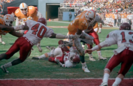 Tennessee running back Reggie Cobb, 34, pulls away from Indiana linebacker Darren Bush, 40, to score in first quarter of their Peach Bowl game at Atlanta Fulton County Stadium in Atlanta, on Jan. 2, 1987.