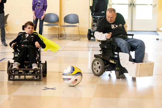 Cosmo Rudd and David Allgood move the ball down court during a Louisville City Power Soccer practice on Saturday. April 20, 2019