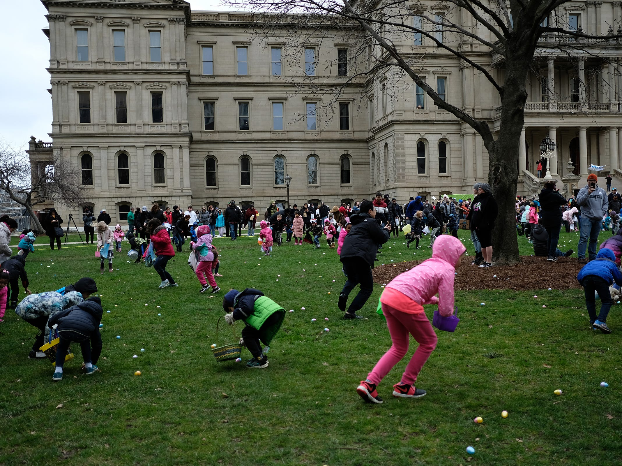 The egg scramble is on as kids try to pick up all the eggs at the annual Lansing Jaycees Easter Egg Hunt at the Capitol Saturday, April 20, 2019.