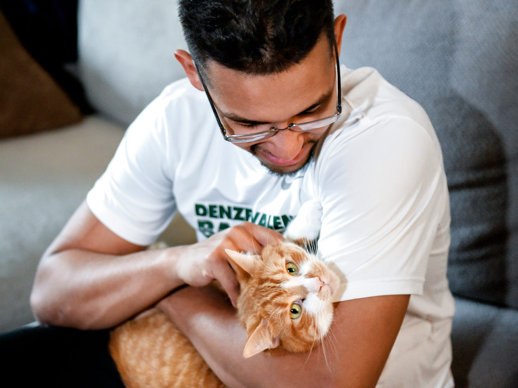 Robert Ray Jr. pets his cat Naruto, a pet he's had for four years, on Friday, April 19, 2019, at his apartment in Okemos.