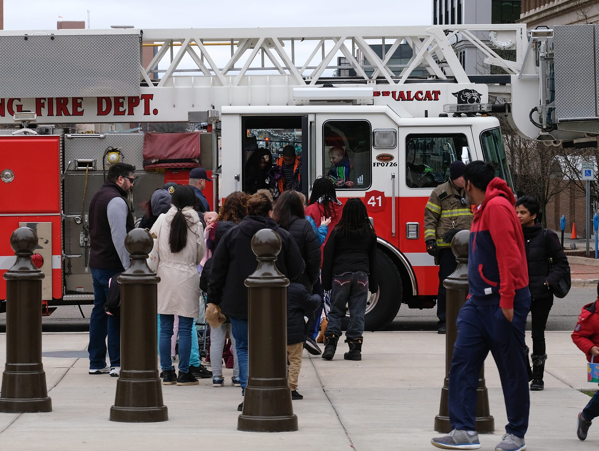 Families check out the Lansing Fire Department ladder truck at the annual Lansing Jaycees Easter Egg Hunt at the Capitol Saturday, April 20, 2019.