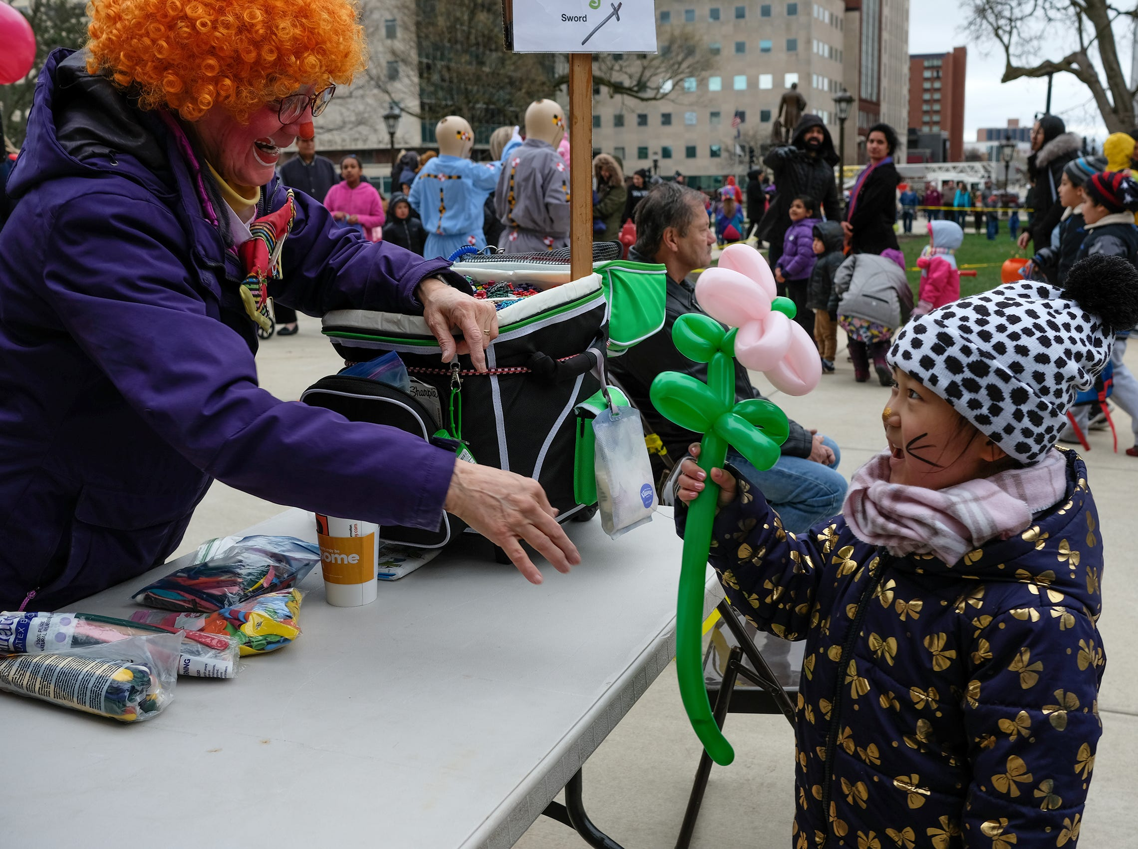Jiexi Li, 5, seems pleased as she gets a flower balloon from one of the clowns at the annual Lansing Jaycees Easter Egg Hunt at the Capitol Saturday, April 20, 2019.