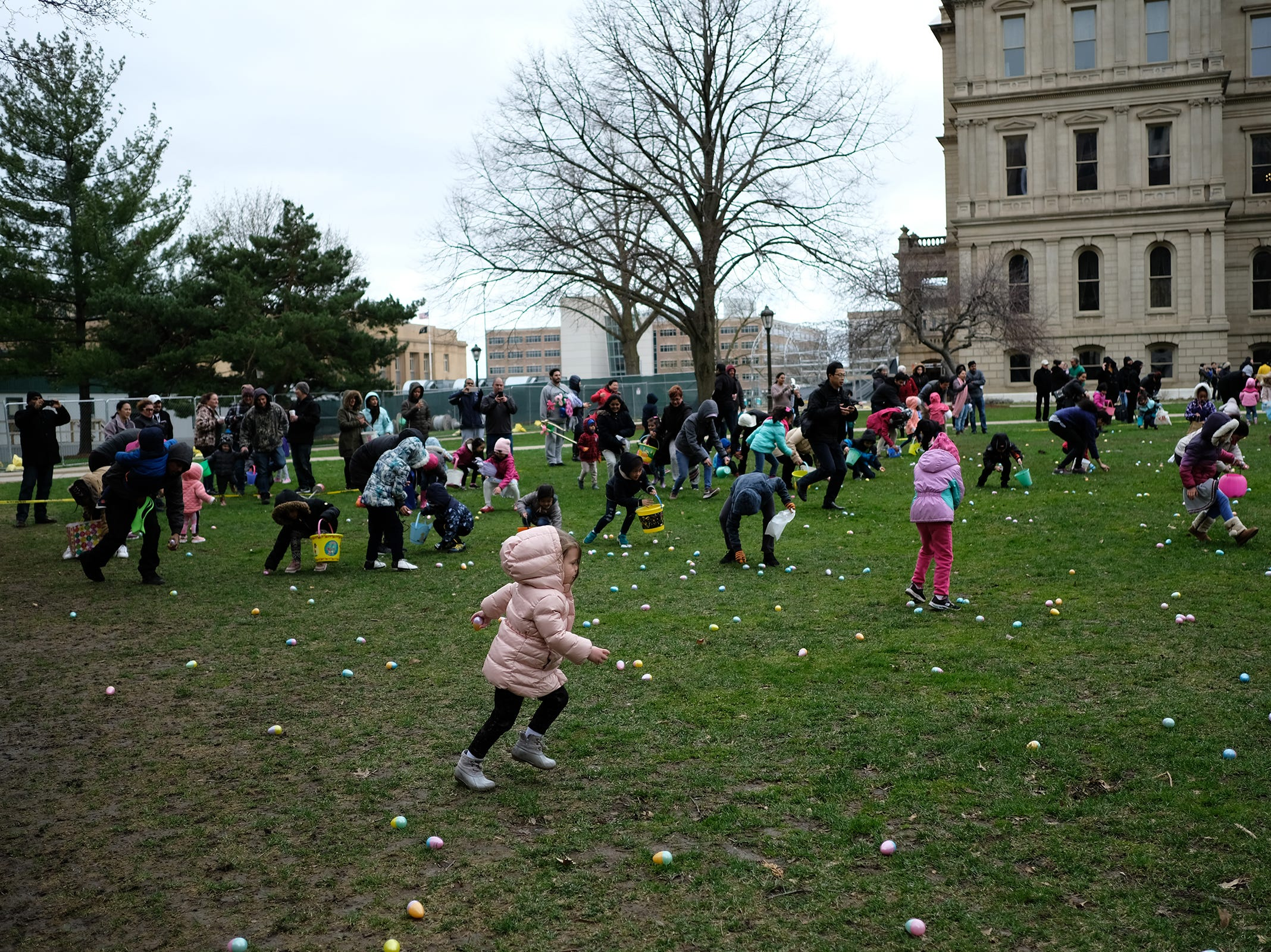 Youngsters quickly gather-up the eggs at the annual Lansing Jaycees Easter Egg Hunt at the Capitol Saturday, April 20, 2019.