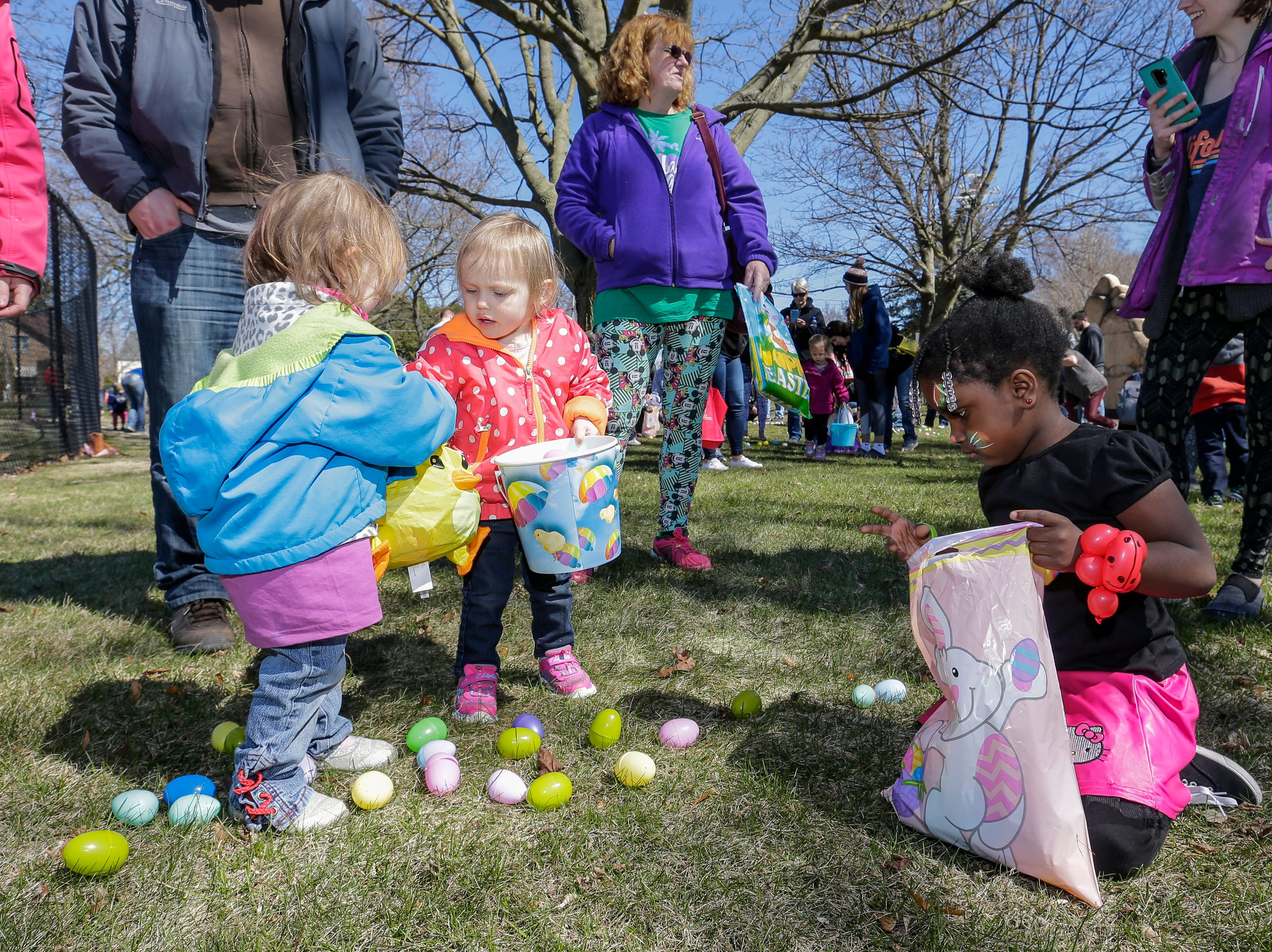 From left, Emery Meives, 2; Sophia Kuehl, 2, and DeRosalind Spencer, 4, grab eggs during the Easter Eggstravaganza at Citizen Park Saturday, April 20, 2019, in Manitowoc, Wis. Joshua Clark/USA TODAY NETWORK-Wisconsin