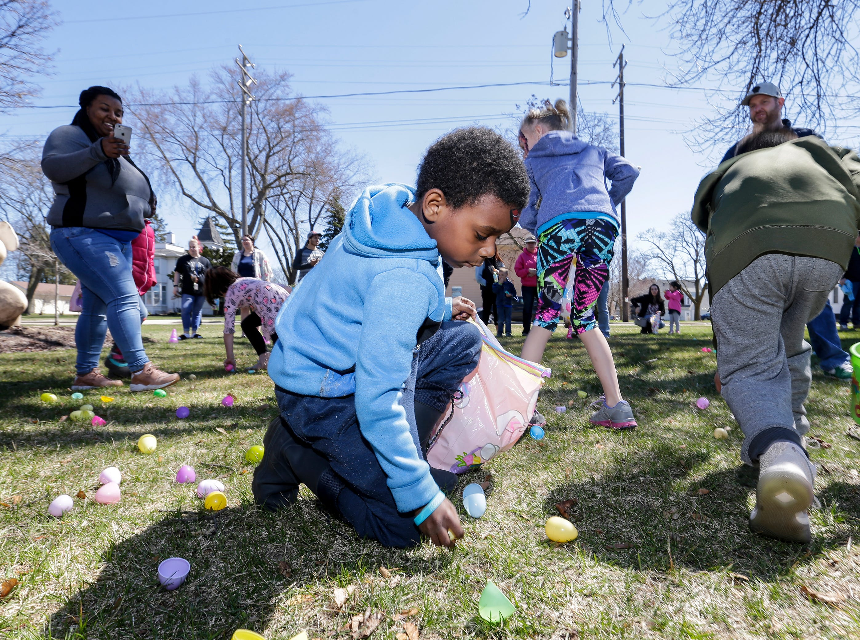 Deshawn Williams, 7, gathers plastic Easter eggs during the Easter Eggstravaganza at Citizen Park Saturday, April 20, 2019, in Manitowoc, Wis. Joshua Clark/USA TODAY NETWORK-Wisconsin