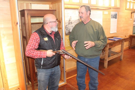 Buddy Huffaker (left), executive director of the Aldo Leopold Foundation, and Jeff Nania, a firearm historian, author and supporter of the foundation, inspect the  20-gauge shotgun formerly used by Aldo Leopold.  The double-barrel shotgun, as well as a .30 caliber rifle used by Leopold, are on display at the foundation near Baraboo, Wisconsin.