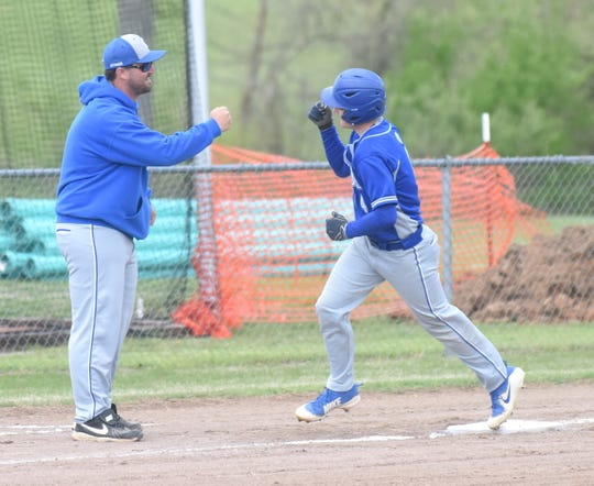 Cotter's Jackson Evans rounds third base and is congratulated by coach Jarod Jefferson after hitting a lead-off home run against Yellville-Summit on Friday.
