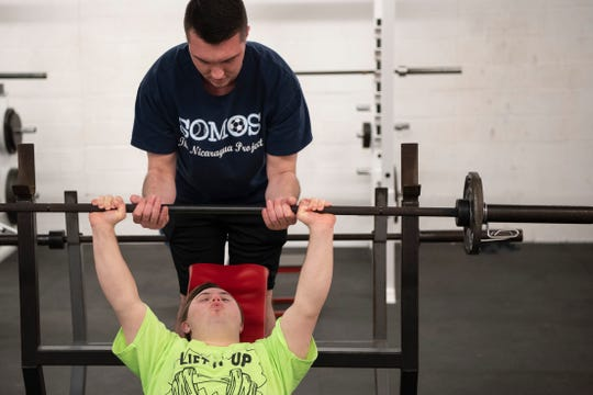 Thomas Leonardis practices a chest press as his brother Joe Leonardis spots him during Lift it Up, a weightlifting program that pairs Challenger athletes with neurotypical buddies at Morris Hills High School on Saturday, April 20, 2019.