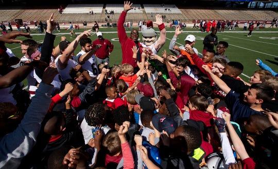 Former Troy University and NFL player DeMarcus Ware works with children during a kids football clinic before the Troy University T-Day spring scrimmage game in Troy, Ala., on Saturday April 20, 2019.