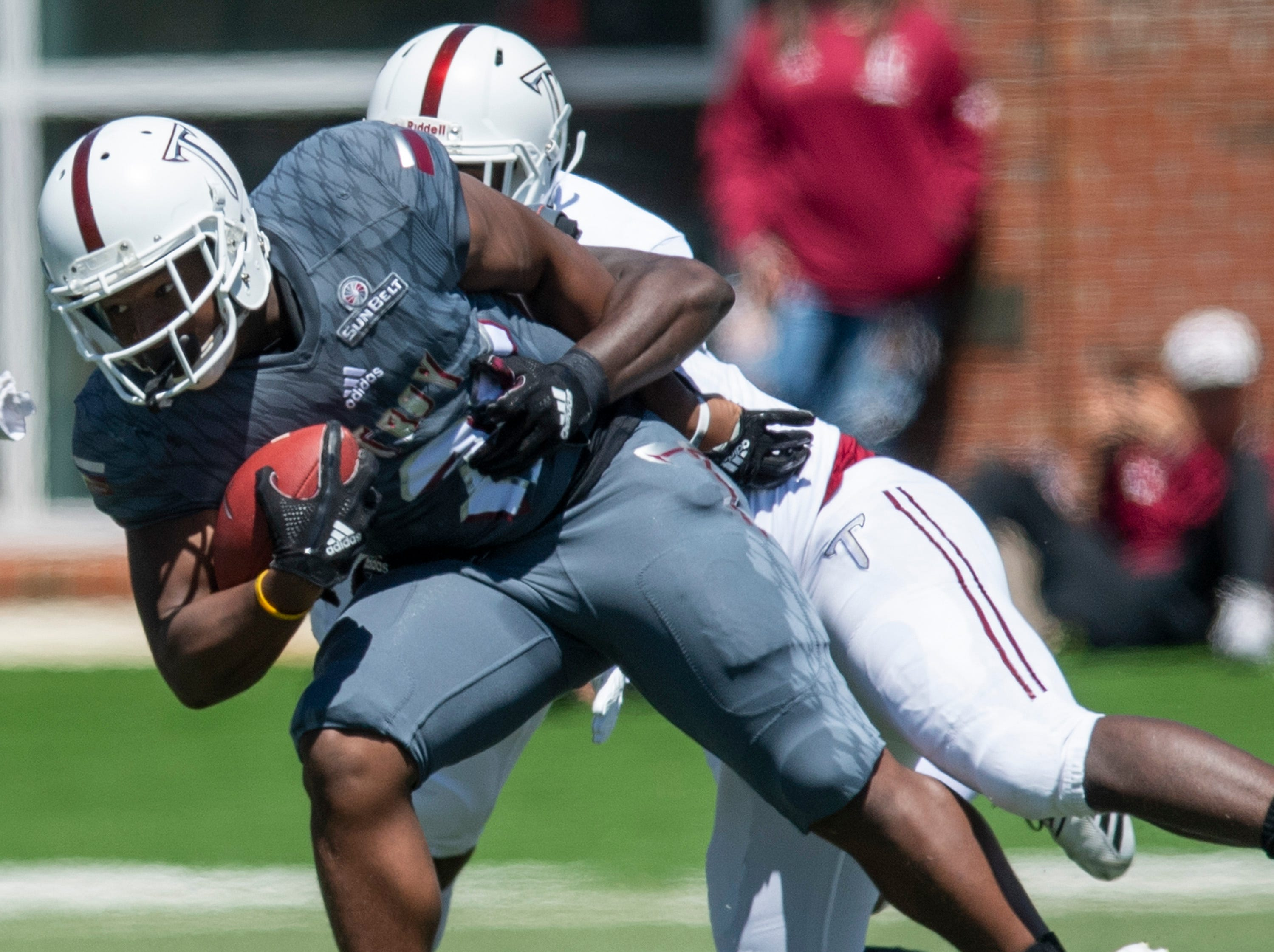 Troy running back Josh Mays (25) is stopped by linebacker Carlton Martial (38) during the Troy University T-Day spring scrimmage game in Troy, Ala., on Saturday April 20, 2019.