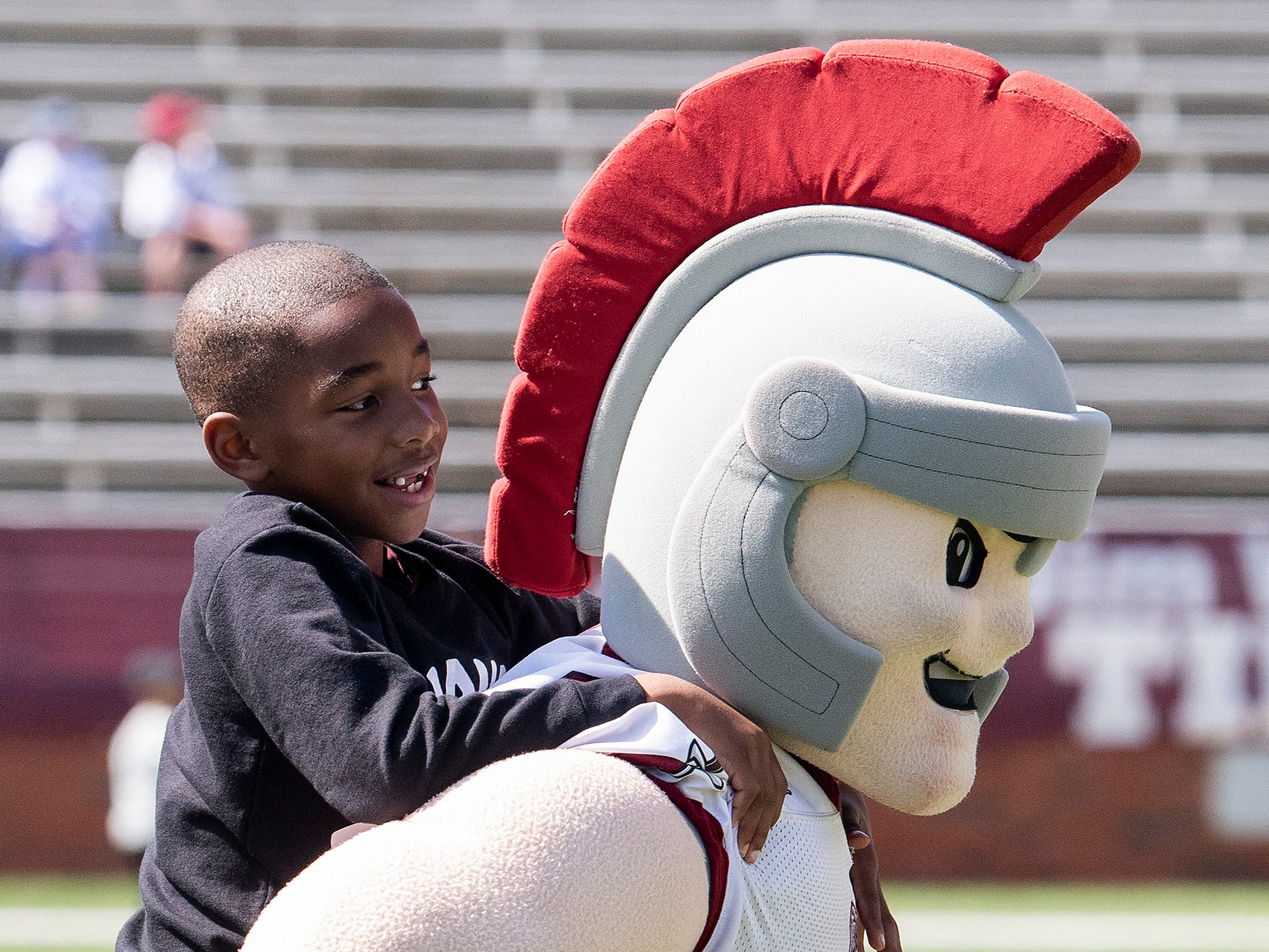 Troy mascot T-Roy gives a kid a ride before the Troy University T-Day spring scrimmage game in Troy, Ala., on Saturday April 20, 2019.