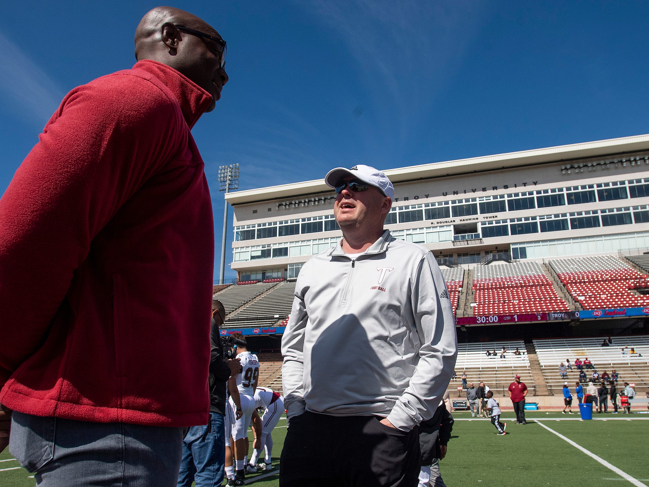 Troy head coach Chip Lindsey chats with former Troy University and NFL player DeMarcus Ware before the Troy University T-Day spring scrimmage game in Troy, Ala., on Saturday April 20, 2019.