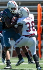 Troy running back Trevon Woolfolk (33) is stopped by linebacker Carlton Martial (38) during the Troy University T-Day spring scrimmage game in Troy, Ala., on Saturday April 20, 2019.