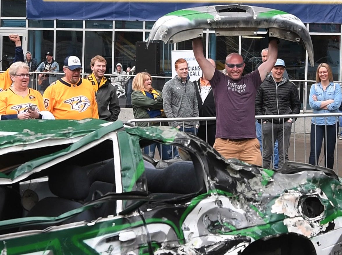 Bryan Roberts holds up the bumper of the Smash Car after knocking it off before the divisional semifinal game against the Stars at Bridgestone Arena Saturday, April 20, 2019, in Nashville, Tenn.