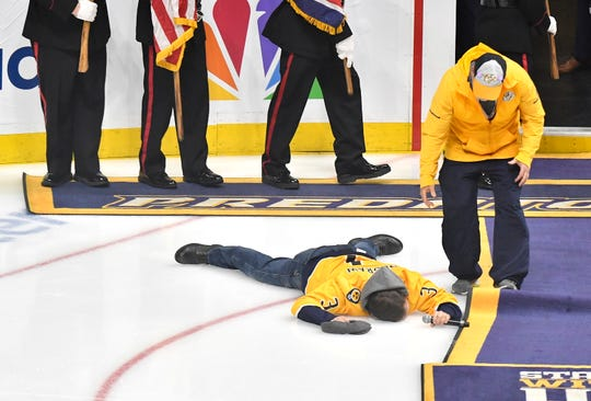 Gavin DeGraw hits the ice after singing the National Anthem before the Predators' divisional semifinal game at Bridgestone Arena in Nashville, Tenn., Saturday, April 20, 2019.