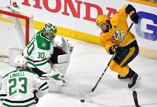 Nashville Predators left wing Filip Forsberg (9) plays the puck defended by Dallas Stars goaltender Ben Bishop (30) during the first period of the divisional semifinal game at Bridgestone Arena in Nashville, Tenn., Saturday, April 20, 2019.