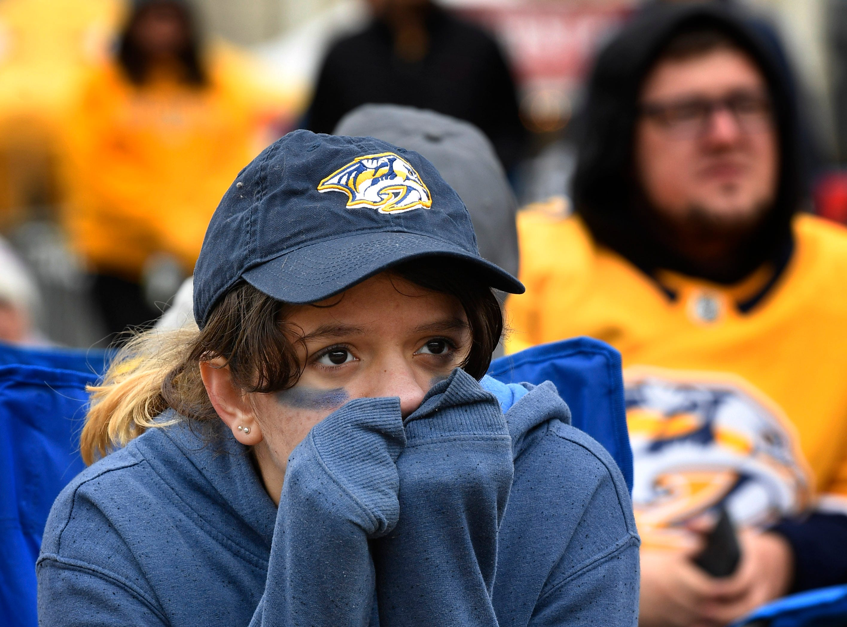 Elizabeth Faria tries to stay warm in chilly weather during the watch party of the divisional semifinal game against the Stars at Bridgestone ArenaSaturday, April 20, 2019, in Nashville, Tenn.