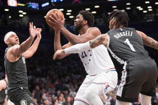 Philadelphia 76ers center Joel Embiid (21) goes to the basket against Brooklyn Nets guard D'Angelo Russell (1)and forward Jared Dudley during the first half of of Game 4 of a first-round NBA basketball playoff series, Saturday, April 20, 2019, in New York.