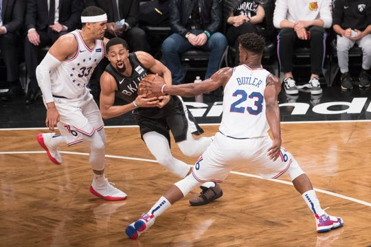 Brooklyn Nets guard Spencer Dinwiddie, center drives against Philadelphia 76ers forward Tobias Harris (33) and guard Jimmy Butler (23) during the first half of of Game 4 of a first-round NBA basketball playoff series, Saturday, April 20, 2019, in New York. (AP Photo/Mary Altaffer)