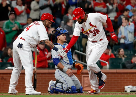 St. Louis Cardinals' Jose Martinez (38) is congratulated by teammate Yadier Molina (4) after hitting a solo home run as New York Mets catcher Wilson Ramos kneels at the plate during the fourth inning of a baseball game Friday, April 19, 2019, in St. Louis.