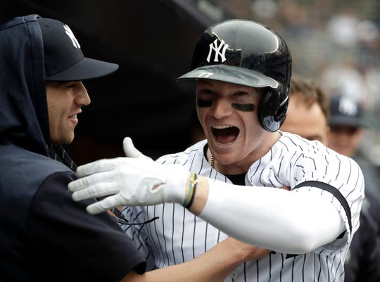 New York Yankees' Clint Frazier, right, celebrates in the dugout with Tyler Wade after hitting a solo home run off Kansas City Royals relief pitcher Heath Fillmyer during the second inning of a baseball game, Saturday, April 20, 2019, in New York.