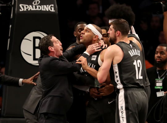 Head coach Kenny Atkinson and Joe Harris #12 of the Brooklyn Nets hold back Jared Dudley #6 at Barclays Center after a foul by Joel Embiid of the Philadelphia 76ers in the third quarter on April 20, 2019 in the Brooklyn borough of New York City.The Philadelphia 76ers defeated the Brooklyn Nets 112-108.