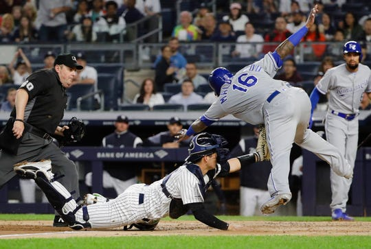 New York Yankees catcher Kyle Higashioka, center, tags out Kansas City Royals' Martin Maldonado at home plate as referee James Williams, left, watches during the third inning of a game Friday, April 19, 2019, in New York.
