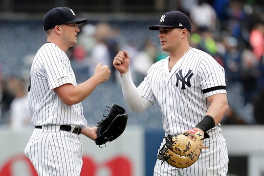 New York Yankees relief pitcher Jonathan Holder, left, fist-bumps first baseman Luke Voit as they celebrate a victory over the Kansas City Royals in a baseball game, Saturday, April 20, 2019, in New York.