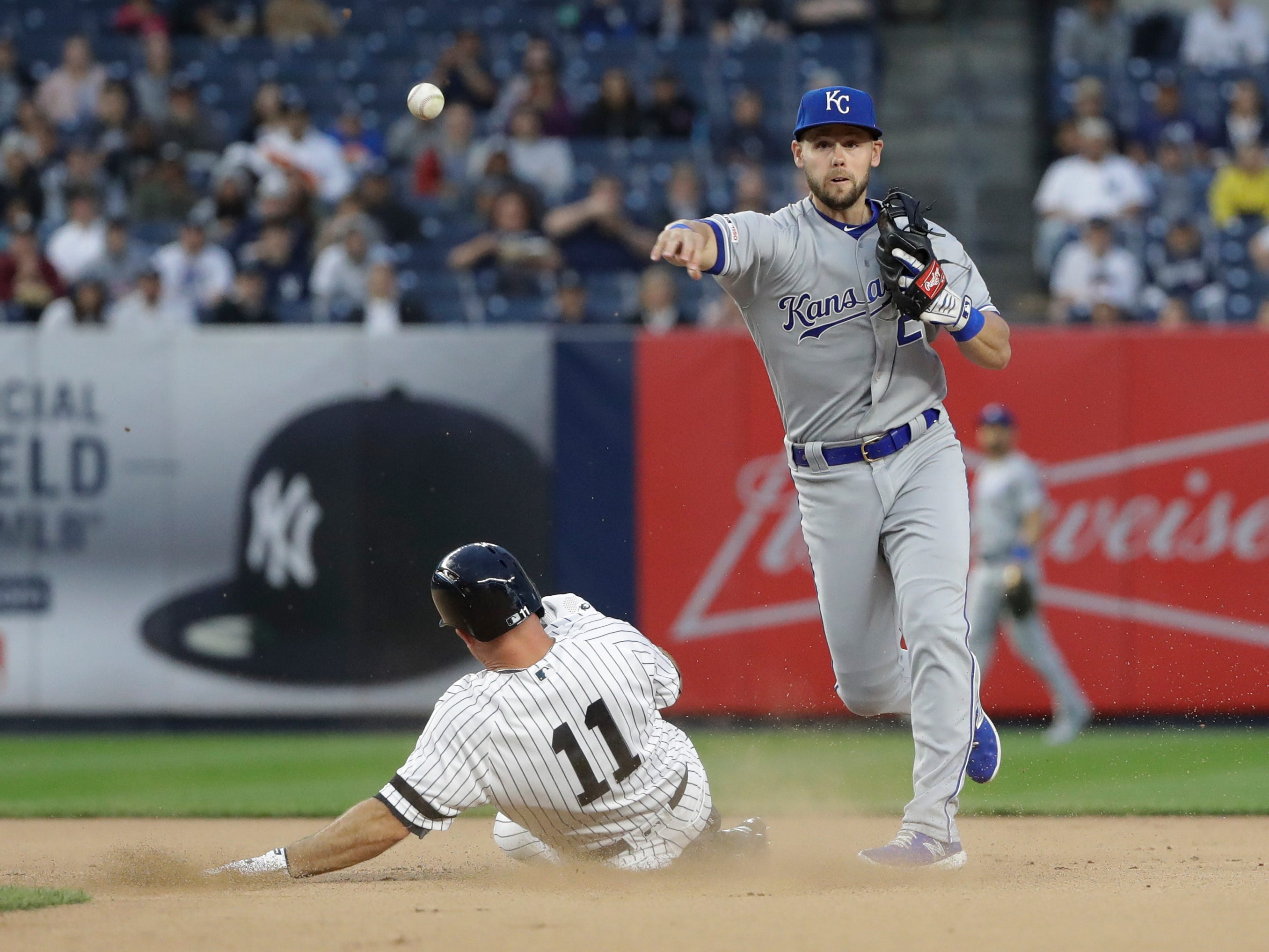 Kansas City Royals' Chris Owings, right, throws out New York Yankees' Aaron Judge at first base after forcing out Brett Gardner, left, for a double play during the first inning of a baseball game Friday, April 19, 2019, in New York.