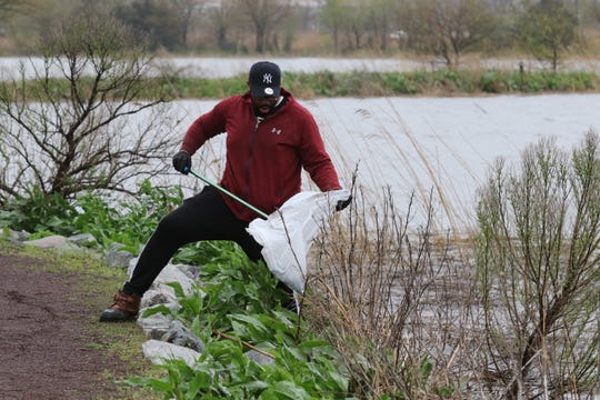Mallik Yamusah of Franklin Lakes collects some garbage from the marsh as he volunteered in the third annual Earth Day Cleanup at Mill Creek Marsh in Secaucus on April 20, 2019.