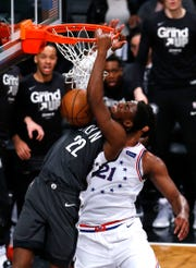 Apr 20, 2019; Brooklyn, NY, USA;  Brooklyn Nets guard Caris LeVert (22) dunks against Philadelphia 76ers center Joel Embiid (21) during the first half at Barclays Center.
