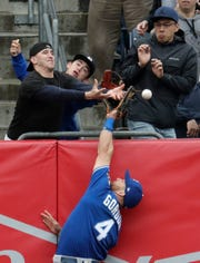A fan interferes as Kansas City Royals left fielder Alex Gordon (4) goes up to try to make a catch on a ball hit by New York Yankees' Gleyber Torres during the third inning of a baseball game, Saturday, April 20, 2019, in New York.