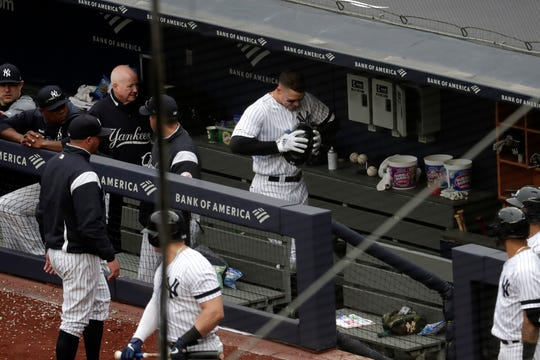 New York Yankees' Aaron Judge, center, clenches his helmet while walking in the dugout after he was pulled from the game after suffering an apparent injury while hitting a single off Kansas City Royals starting pitcher Glenn Sparkman during the sixth inning of a baseball game, Saturday, April 20, 2019, in New York.