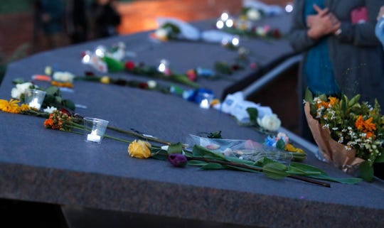 Tea lights illuminate the plaques adorned with flowers during a vigil at the memorial for the victims of the massacre at Columbine High School nearly 20 years ago Friday, April 19, 2019, in Littleton, Colo.