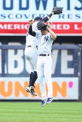 Apr 20, 2019; Bronx, NY, USA; New York Yankees center fielder Mike Tauchman (39) and right fielder Tyler Wade (14) celebrate the 9-2 victory over the Kansas City Royals at Yankee Stadium.