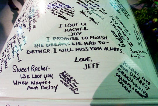 FILE - In this April 24, 1999, file photo, the casket bearing Columbine High School shooting victim Rachel Joy Scott is signed with notes of remembrance from family members as it sits at the Trinity Christian Center in Littleton, Colo. Twelve students and one teacher were killed in a murderous rampage at the school on April 20, 1999, by two students who killed themselves in the aftermath.