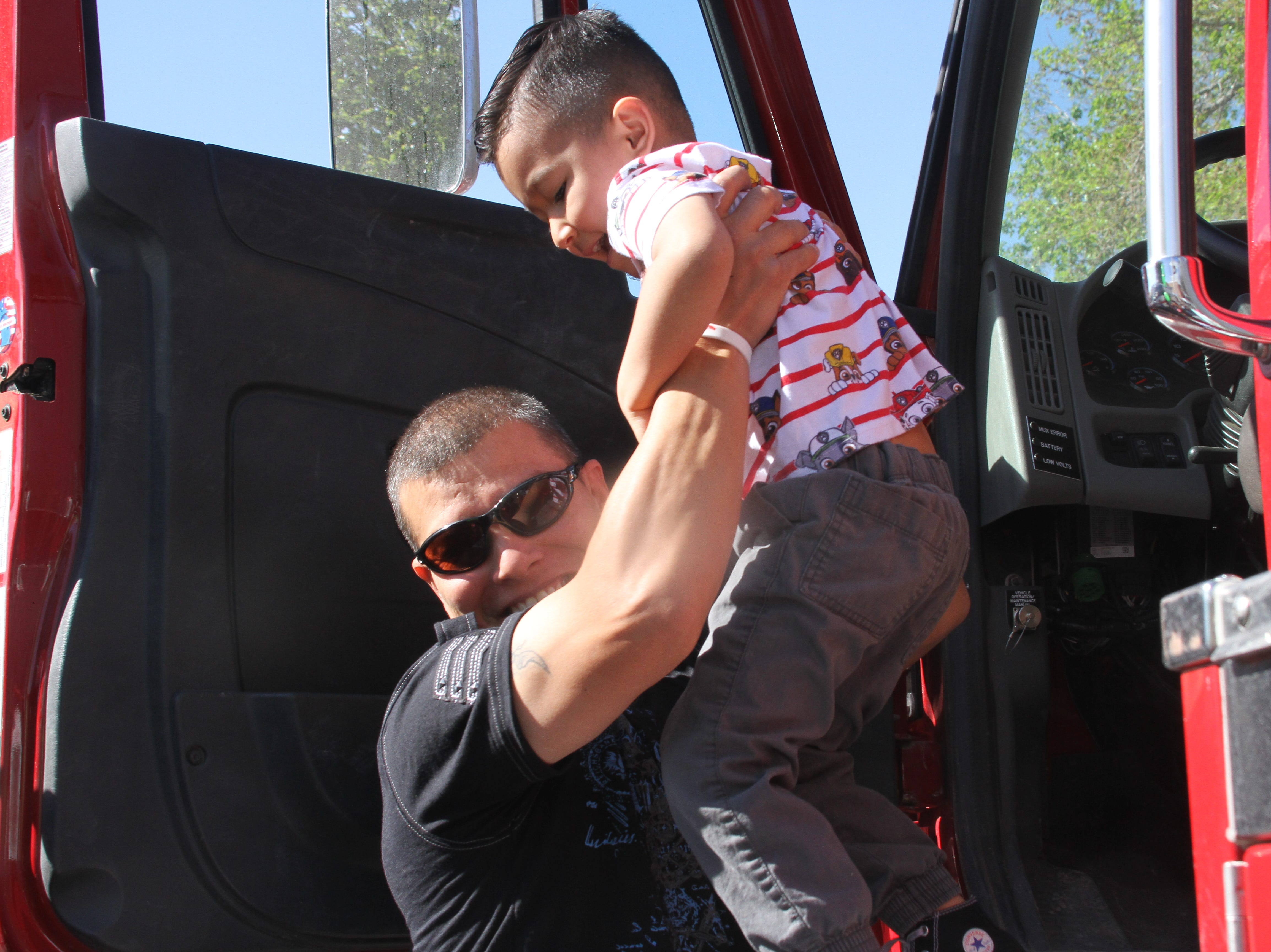 4-year-old Angel Nunez being lifted out of Deming Fire's fire truck by family friend, Adam Chacon.