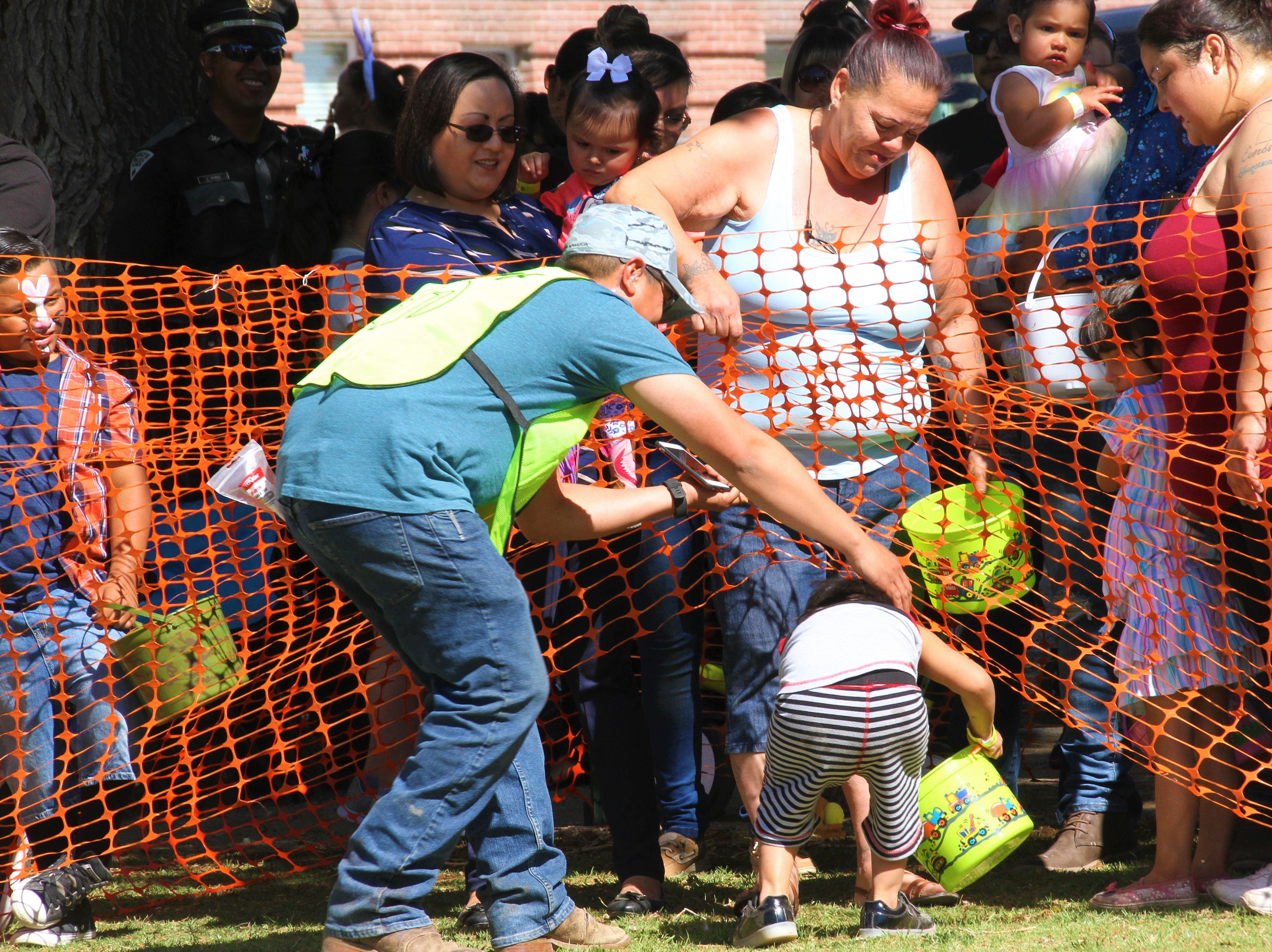 Jeremiah Granillo, 2, sneaking off to get first dibs on Easter eggs. Here, Deming First Assembly of God volunteer escorts Jeremiah back to the line with grandma Sandra.