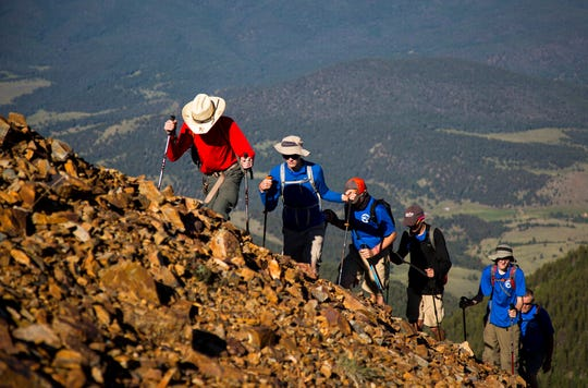 In this July 18, 2017, photo provided by the Philmont Scout Ranch, a crew hikes up Baldy Mountain, the tallest peak on the ranch near Cimarron, New Mexico. Philmont is rebuilding following a devastating wildfire that burned nearly 44 square miles in 2018. Backcountry trails were wiped out along with trail camps.