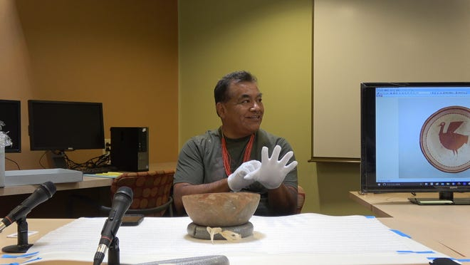 Hopi artist Gerald Lomaventema puts on gloves as he prepares to handle prehistoric Mimbres pottery. The pottery will be on display at New Mexico State University's American Indian Student Center beginning Friday, April 26. Lomaventema and other Hopi artists will have a panel discussion from 1–4 p.m. to share their interpretations of the meaning of the pottery designs.