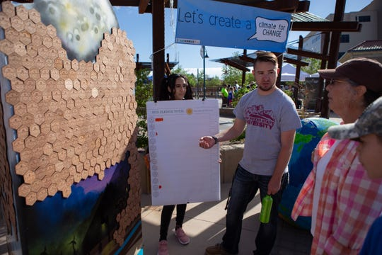 Caleb Baca and Jocelyn Villa of the Associated Students of New Mexico State University Business Council talk about Eco Pledges to interested Earth Day participants during the Earth Day and March for Science events on the Downtown Plaza on Saturday, April 20, 2019.