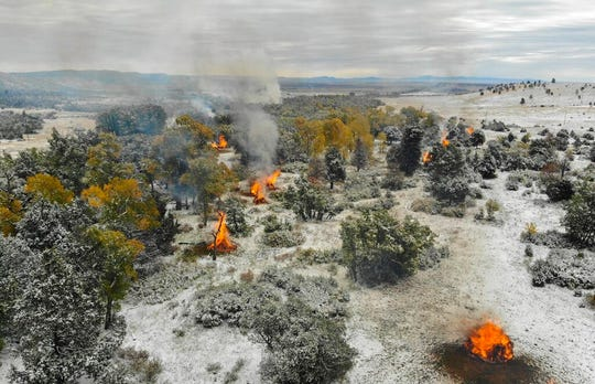 This Oct. 15, 2018, photo, provided by Philmont Scout Ranch shows piles of slash being burned as part of an effort to clear out extra fuel. The historic ranch near Cimarron, New Mexico, is rebuilding following a devastating wildfire that burned nearly 44 square miles in 2018. Backcountry trails were wiped out along with trail camps.