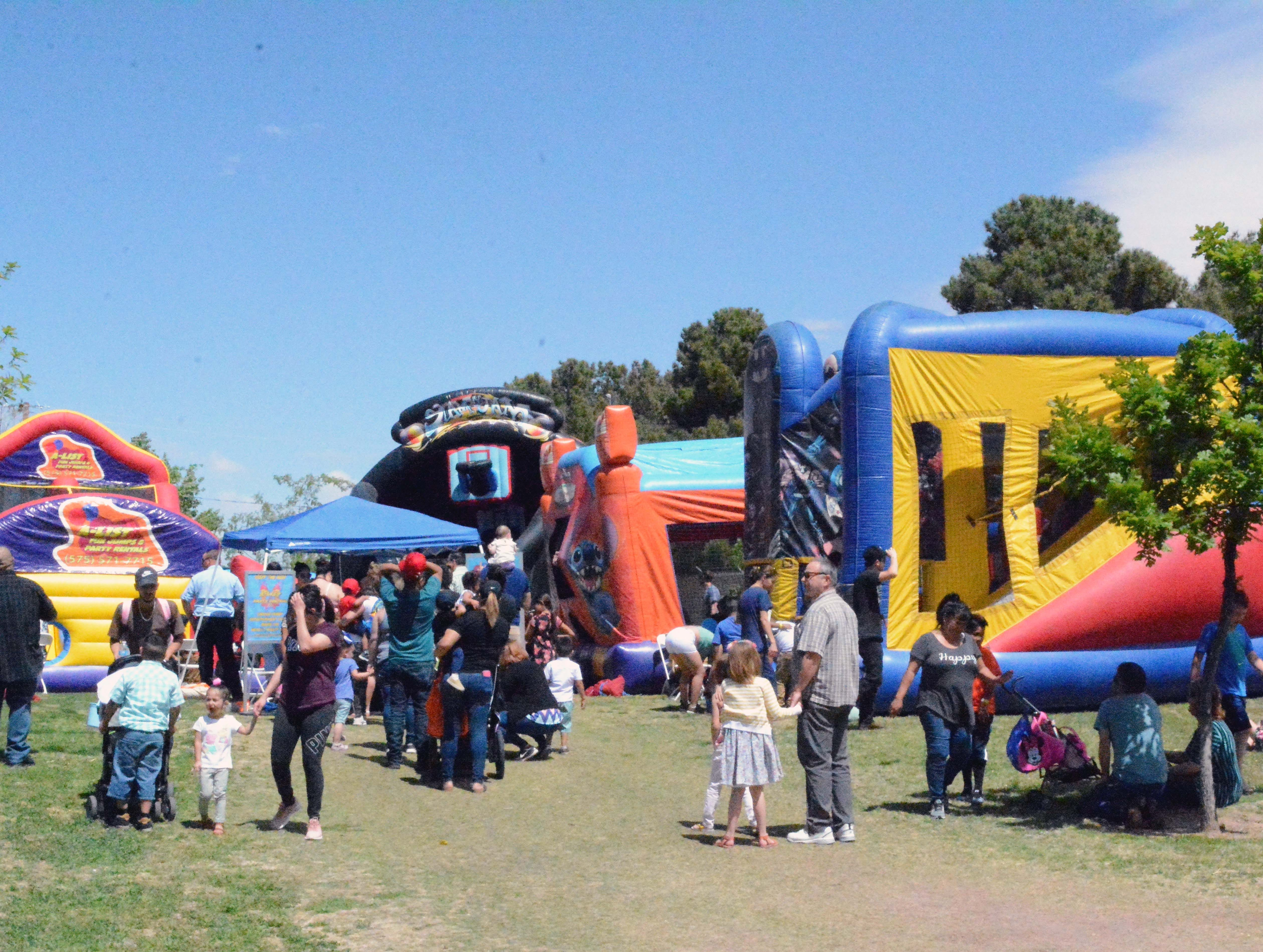 A line forms for the inflatable play area during SpringFest at Young Park on Saturday, April 20, 2019.