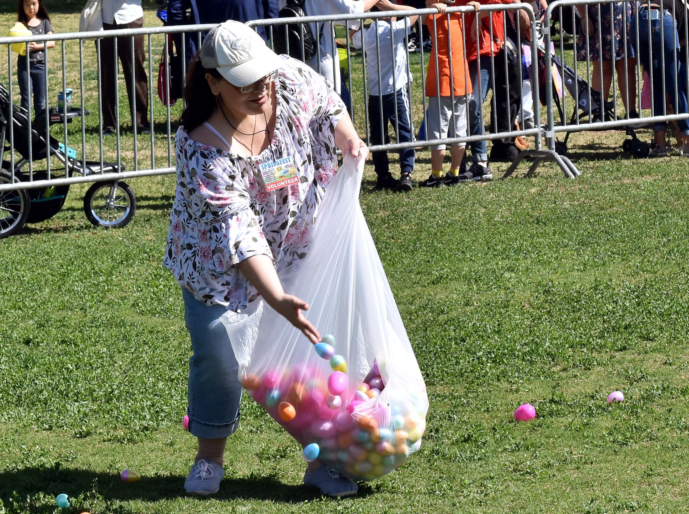 Cindy Quillin scatters eggs for what she says is her last time after 10 years as a volunteer. This year's SpringFest was held at Young Park on Saturday, April 20, 2019.