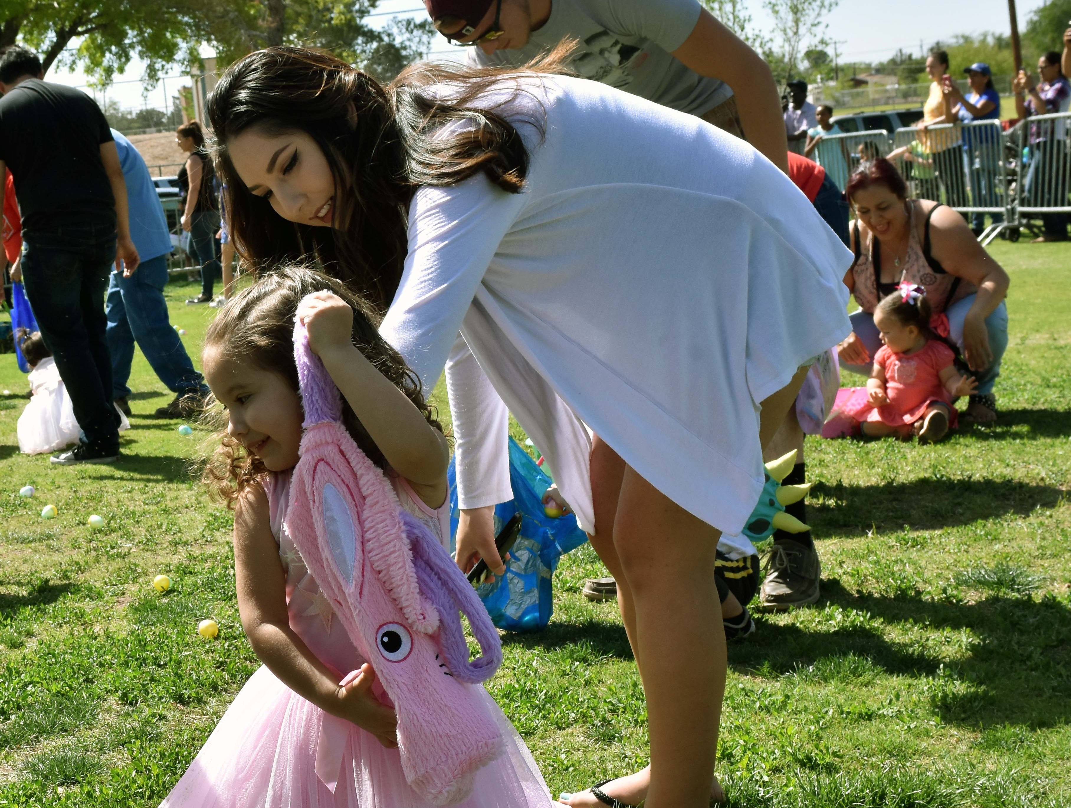 Natalie Lara fills her basket as her mother Jamie Lara helps her along during this year's SpringFest at Young Park on Saturday, April 20, 2019.