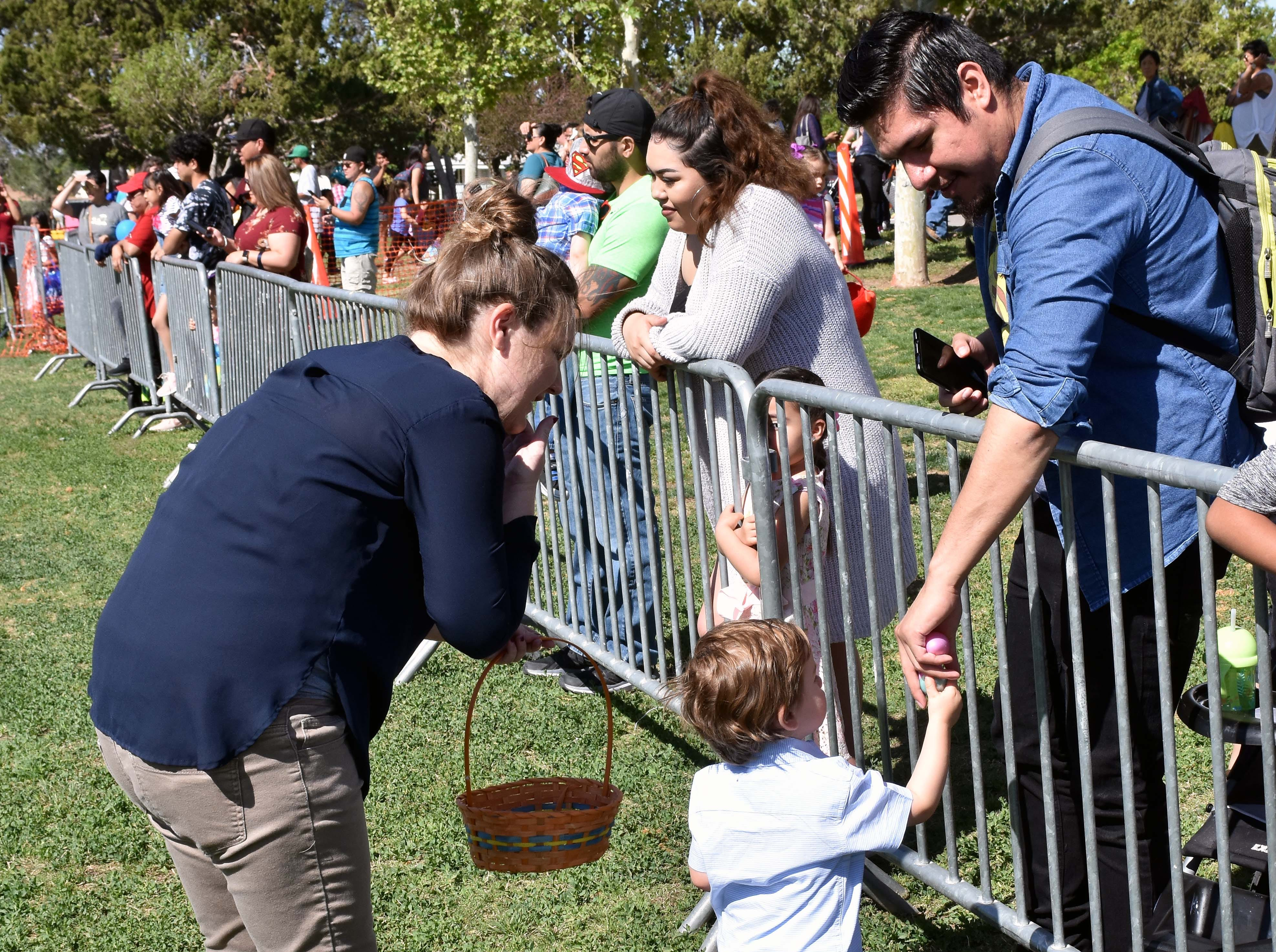 Max Salazar, 1 and a half, shares his Easter eggs with Chris Salazar as his mother Jennifer Stacy watches during this year's SpringFest at Young Park on Saturday, April 20, 2019.