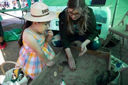 Kimberly Barry of the Southwest Environmental Center shows Olive, 4, how to make animal tracks during the Earth Day and March for Science events on the Downtown Plaza on Saturday, April 20, 2019.