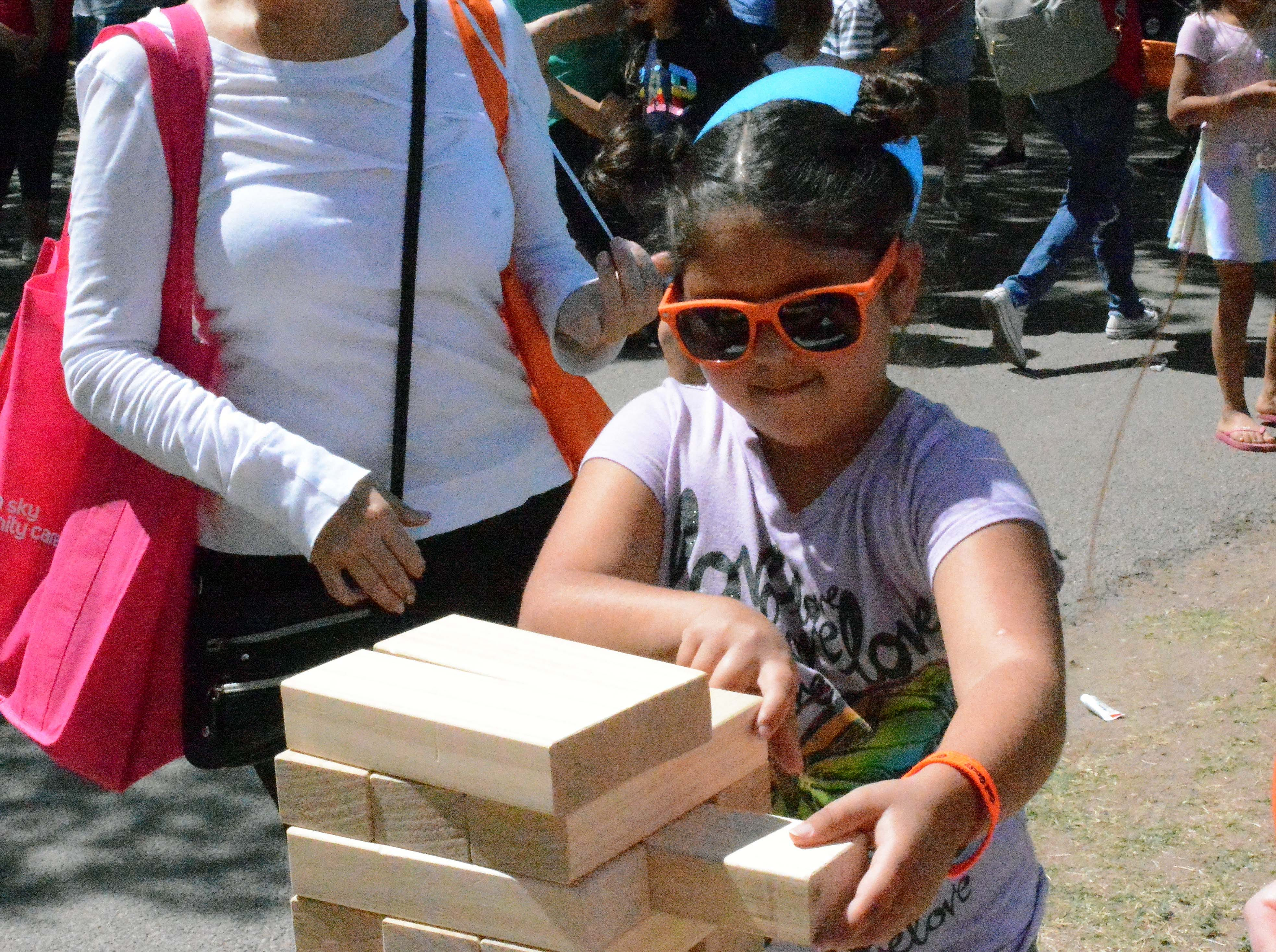 Adrienne Bustamante, 8, puts her skills to work in a game of Jenga during SpringFest at Young Park on Saturday, April 20, 2019.