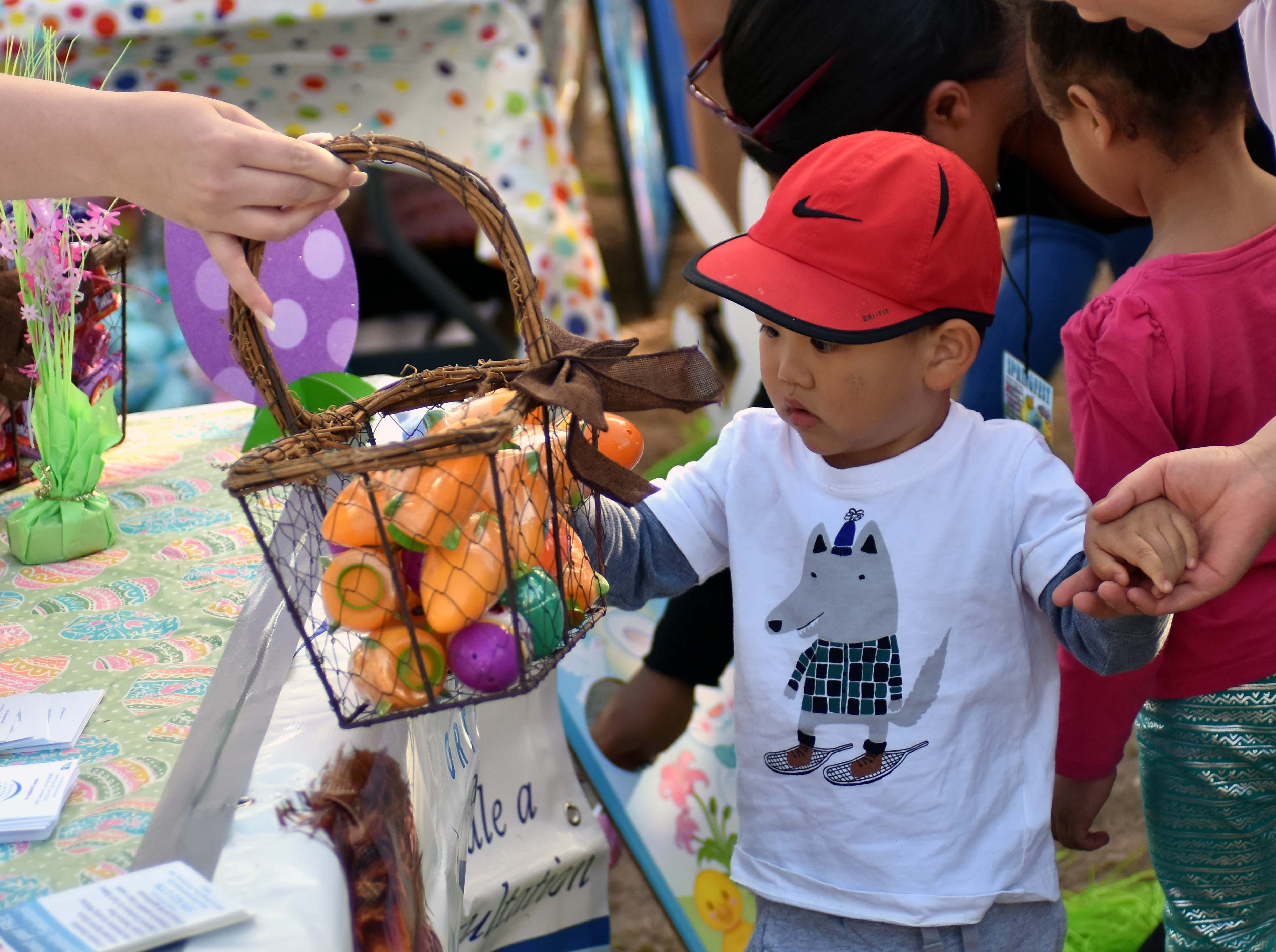 Patrick Wu, 2 and a half, gets to pick an egg from a basket provided by Children's Dental Clinic during SpringFest at Young Park on Saturday, April 20, 2019.